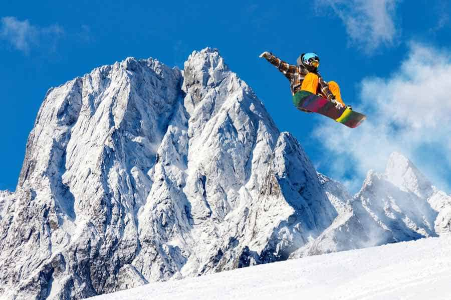 Snowboarder Jumping next to mountain